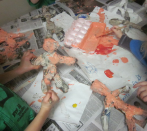 painting their paper mache sculptures